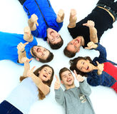 Young people lying down,. Gesturing thumb up sign Royalty Free Stock Photography