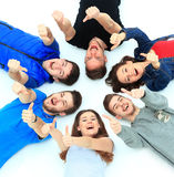 Young people lying down. Gesturing thumb up sign Royalty Free Stock Images