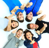 Young people lying down. Gesturing thumb up sign Stock Photo