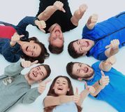 Young people lying down. Gesturing thumb up sign Stock Images