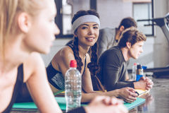 Young people lying on yoga mats and exercising at the gym Stock Photo