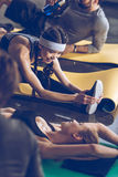 Young people lying on yoga mats and exercising at the gym Royalty Free Stock Photography