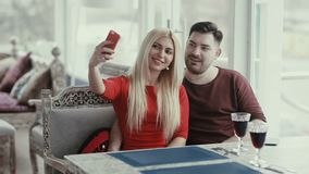 Young people make joint selfie. Young woman doing a joint photo with his companion. Man sitting next to the blonde on a sofa in the restaurant stock footage