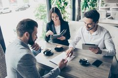 Young people are making a deal with lawyer about their business. In cafe with cups of coffee. Men is going to sign contract to complete the deal, reading it Royalty Free Stock Photos