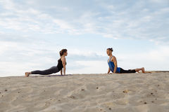 Young people man and woman doing yoga at sunset in the desert. royalty free stock photo