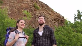 Couple traveling with backpacks in the mountains. Young people,man and woman are traveling with backpacks in the mountains stock footage