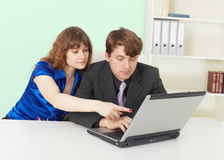 Young people - man and woman working in office. Young people - a man and woman working in an office with computer Royalty Free Stock Photo