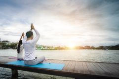 Young people meditate on the waterfront on a wooden bridge for g stock photos