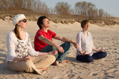 Young people meditating on the beach Royalty Free Stock Photography