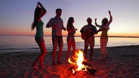 Young people meet dawn near campfire. stock video footage