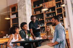 Young people meeting at coffee shop. Group of friends sitting around table and waiter serving coffee at cafe. Young people meeting at coffee shop Stock Images