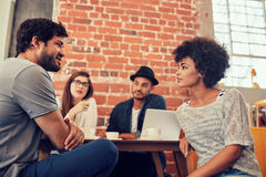 Young people meeting at a coffee shop. Portrait of young friends sitting at a cafe table and talking. Group of young people meeting at a coffee shop Stock Image