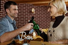 Young people meeting in pub. Clinking beer bottles, smiling Stock Photo