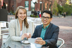 Young people with mobile phone in cafe Royalty Free Stock Photos