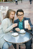 Young people with mobile phone in cafe Royalty Free Stock Photography
