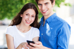 Young people with mobile phone outdoors Royalty Free Stock Photo