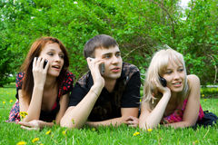Young people on the mobile phones. Three young friends calling on mobile phones Royalty Free Stock Images