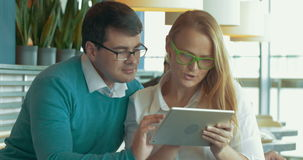 Young people with pad choosing something in. Young man  and woman in glasses sitting in cafe and using tablet computer. They surfing the Internet to find stock footage