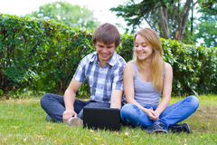 Young people in the park. Working with their lap top Royalty Free Stock Image