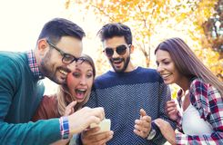 Young people in park with smart phone Royalty Free Stock Photo