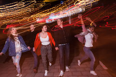 Young people party in city. Free nightlife. Happy students outdoors, strong friendship, bright lights background Royalty Free Stock Photography
