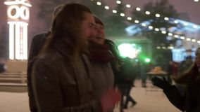 Young people partying at Christmas concert city square. Friends have fun dancing at New Year market fairground outdoors