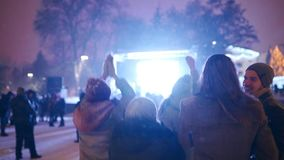 Young people partying at Christmas concert on city square. Friends have fun jumping with raised hands and dancing with