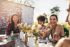 Young people partying at garden restaurant. Young people partying in a restaurant outdoors. Multiracial friends sitting together around a table and smiling royalty free stock image