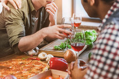 Young people partying at home. Young people partying, eating pizza and drinking wine at home party Royalty Free Stock Photos