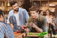 Young people partying at home. Young people partying, eating pizza and drinking wine at home party Royalty Free Stock Photo