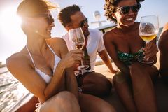Young people partying on the private boat. Beautiful women with friends having fun on a yacht, drinking wine and smiling. Young people partying on the private Stock Image