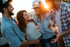 Young people partying on terrace with drinks at sunset. Young men and women enjoying drinks on rooftop Stock Photo