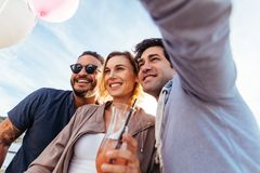 Young people partying together and taking selfie. Group of men and women on rooftop party taking selfie stock photo