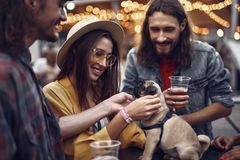 Free Young People Petting Little Pug While Standing At The Table Stock Images - 130111744