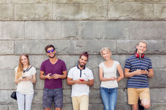 Young people with phones. Young people with mobile phones standing beside wall Royalty Free Stock Photography