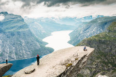 Young People Are Photographed Standing On A Rock Trolltunga - Troll Tongue Royalty Free Stock Image