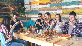 Young people photographing food in rustic restaurant – happy friends taking picture of pizza and hamburgers with mobile phones