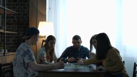 Young people play board game using dice and chips. Group of young hipster people playing board game using dices and chips while sitting at the table in domestic stock video