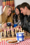 Young people play chess winter cottage countryside Stock Photo