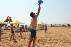 Young people play a flying disc on the beach in Kerch royalty free stock photography