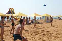 Young people play a flying disc on the beach in Kerch Stock Photography