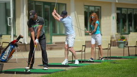 Young people play golf near the clubhouse stock video