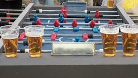 Young people play table football and drink beer outdoors. Figures of footballers move left and right people playing. Foosball. Table soccer plaers. Table stock video