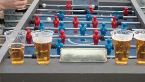 Young people play table football and drink beer outdoors. Figures of footballers move left and right people playing. Foosball. Table soccer plaers. Table stock video footage