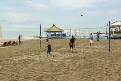 Young people playing beach volleyball on the sand by the sea Royalty Free Stock Images