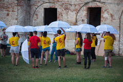 Young people playing a game with white umbrellas Stock Photos