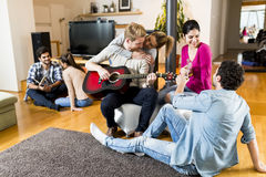 Young people playing guitar and  having a party in the house Stock Image