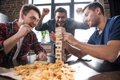 Young people playing jenga game Stock Images