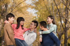 Young people playing piggyback in park Stock Photo