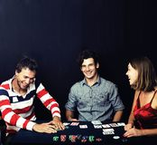 Young people playing poker on black background Stock Photo